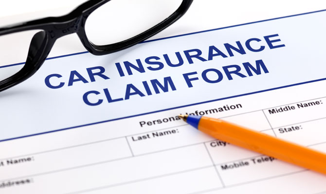 car insurance claim form with pen and glasses