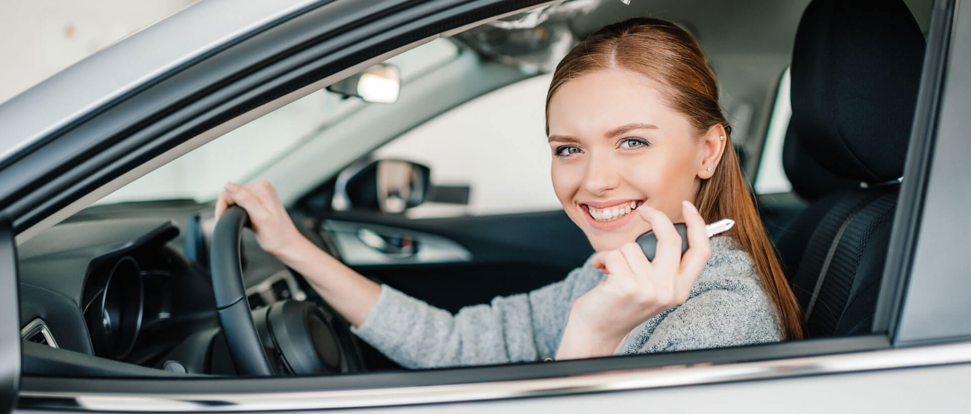 redhead woman in new car with keys