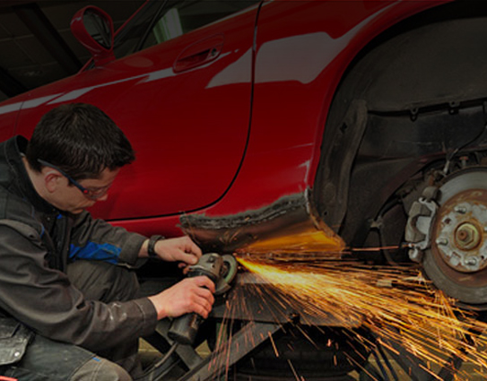 car mechanic repair technician welding red car damage