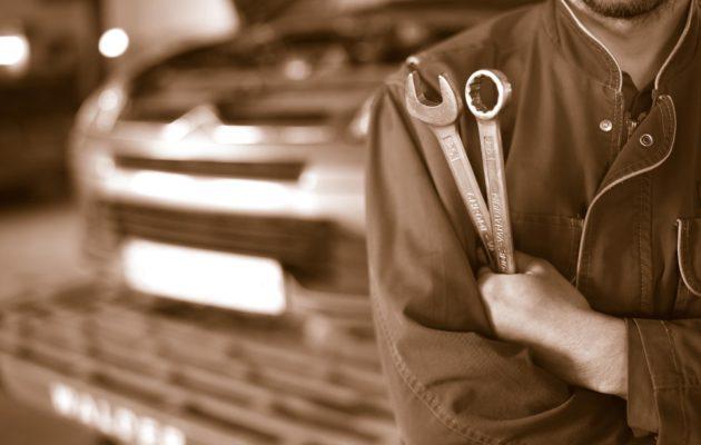 sepia car mechanic technician holding wrench