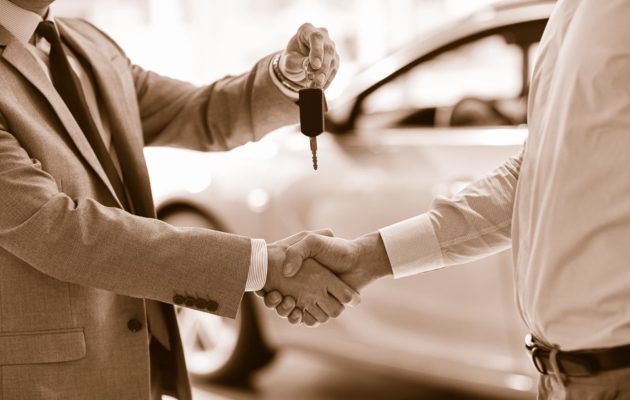 two men shaking hands car dealership new car sepia